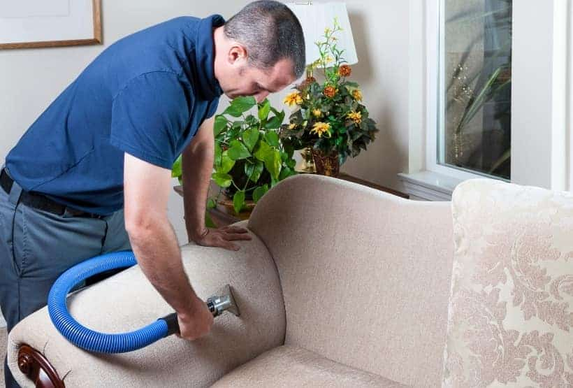 clean fabric sofa with vacuum cleaner